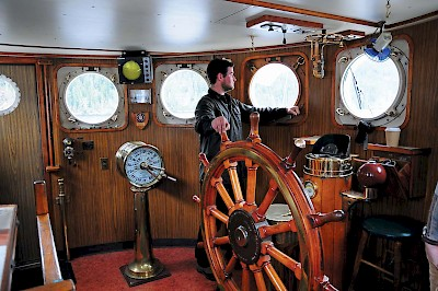 Captain Spencer Larsen in the wheelhouse of the MV Uchuck III navigating the waterways of Nootka Sound.